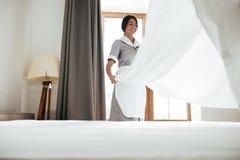 Hotelowa gosposia zmienia łóżkowego prześcieradło obrazy royalty free