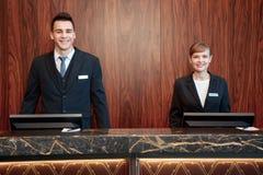 Hotelowi recepcjoniści za kontuarem Zdjęcia Royalty Free