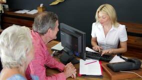 Hotelreceptionnist Helping Senior Couple om binnen te controleren stock videobeelden