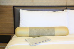 Hotelroom. Bed with newspaper and pillows Royalty Free Stock Photo