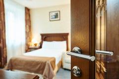 Hotelruimte met open deur en slaapkamer op achtergrond Stock Fotografie