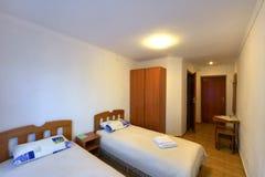 Hotelruimte met twee bedden houten garderobe en lijst royalty-vrije stock afbeelding