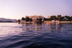Hotels on the banks of lake pichola udaipur at dusk. The beautiful lake city of Udaipur offers many modern and traditional hotels for stay Royalty Free Stock Photo