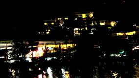 Hotels in mountains at night with lights on. Background of ripples In sea. Video shift up motion 1920*1080 stock video