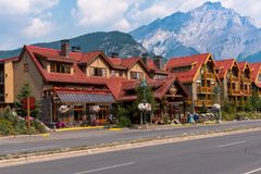 Hotels and Restaurants in Banff. Banff, Canada--August 2, 2018.  Picturesque hotels and restaurants line the main street of Banff with the mountains in the Stock Photos