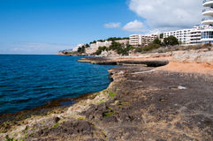 Hotels of Santa Ponsa, Majorca, Spain. Image shows coast of Santa Ponsa, Majorca, Spain. Blue sea on the right, hotels and some stones on the right, and blue sky Royalty Free Stock Photos