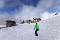 Hotels on ski resort and snowboarder on slope Royalty Free Stock Photo