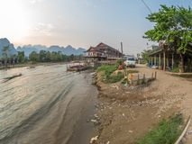 Nam Song River, Laos. Hotels, tourists and trash on the banks of the Nam Song River . Impressive limestone mountains in the background. Blue sky with light cloud stock image