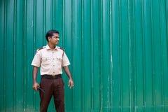 Hotelveiligheidsagent in Sri Lanka tegen een groene omheining stock foto