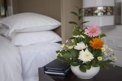 Hotelzimmer mit Bett und Blumen stockfoto