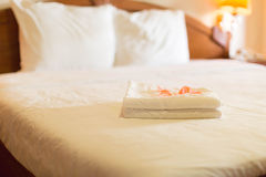 Hotelzimmer mit einem Stapel Tüchern mit den rosafarbenen Blumenblättern Lizenzfreies Stockbild