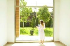 Hotelzimmer voll von Sonnenlichtsonnenstrahlen Optimistischer Anfang Blonde Frau, gemütliche Haupt-Kleidung, Morgentageslicht Neu Lizenzfreie Stockbilder