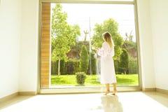 Hotelzimmer voll von Sonnenlichtsonnenstrahlen Optimistischer Anfang Blonde Frau, gemütliche Haupt-Kleidung, Morgentageslicht Neu Stockfoto