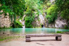 The Hotnitsa Falls Kaya Bunar in Bulgaria, with turquoise waters, a bench, and green, luxurious vegetation grown everywhere. Authentic, natural, touristic spot stock photo
