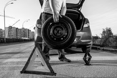 Hoto of man carrying spare wheel against broken car Royalty Free Stock Photography