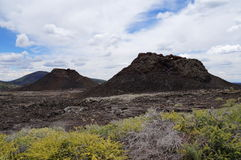 Hotspot volcanic chain: chain of volcanic cones in one line. Two spatter cones and one cinder cone rising above a landscape of black volcanic basalt rock from stock photos