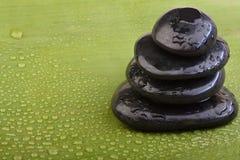 Hotstones mojados en la hoja verde del plátano Fotografía de archivo