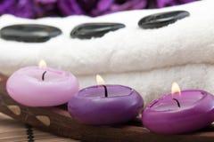 Hotstones op handdoek met purpere kaarsen (2) Stock Fotografie