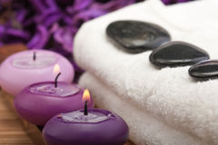 Hotstones on towel with purple candles (1) Stock Photography