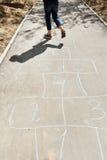 Houblon de fille dans le jeu de marelle sur l'allée urbaine Photo stock