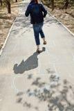 Houblonnage de fille dans le jeu de marelle sur l'allée urbaine Photos libres de droits
