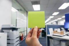 Houd een groene post-it in hand Stock Fotografie