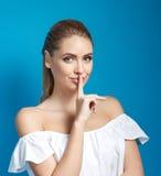 Houd mijn geheim! De mooie jonge vinger van de vrouwenholding op lippen en het bekijken camera royalty-vrije stock foto's