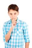 Houd mijn geheim! Ernstige die tienerjongen in de holdingsvinger van het plaidoverhemd op lippen en het bekijken camera op witte  Royalty-vrije Stock Foto's