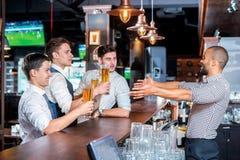 Houd uw bier Vier vrienden die bier drinken en pret hebben togeth Stock Afbeelding