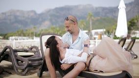 Houd van het paar die op de chaise zitkamer van elkaar genieten het bedrijf van ` s door het overzees en bergen op de achtergrond stock video