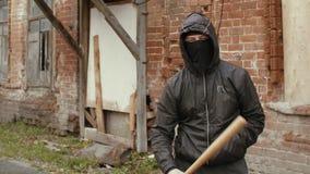 Houden het het Hooliganin zwarte masker en jasje met kap in honkbalknuppel op straat stock footage