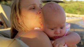 Houdend dochter van de moeder van de kussende baby openlucht stock video