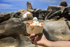 Houdend een kokosnoot met orchideebloem die wordt verfraaid Stock Foto's