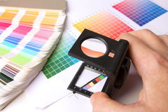 Houdend een lupe en examing kleuren Stock Afbeelding