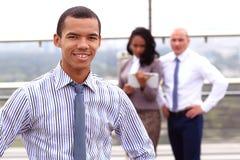 Houdend een tablet, bevindt een jonge knappe zwarte zakenman zich buiten een bedrijfsgebouw, vol vertrouwen kijkend stock afbeelding