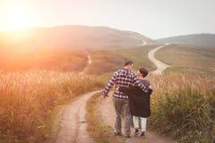 Houdend van aantrekkelijk paar die op middelbare leeftijd op de weg weggaan stock foto's