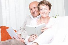 Houdend van het gelukkige paar ontspannende thuis lezen stock afbeelding