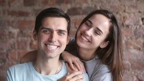 Houdend van jong camera bekijken, en paar die binnen glimlachen omhelzen stock video