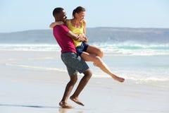 Houdend van jong paar die pret op het strand hebben royalty-vrije stock afbeelding