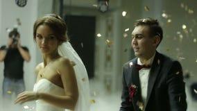 Houdend van jonggehuwdepaar die die de eerste dans bij huwelijk dansen met confettien wordt gehuld stock video