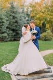 Houdend van jonggehuwdepaar die in zonnig park bij steeg lopen Charmante bruid die haar bruids boeket houden Royalty-vrije Stock Foto's