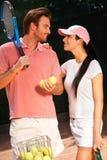Houdend van paar bij tennisbaan het glimlachen Stock Afbeeldingen