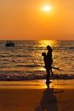 Houdend van paar bij zonsondergang in het overzees Stock Foto's