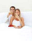 Houdend van paar dat Champagne met aardbeien drinkt Royalty-vrije Stock Fotografie