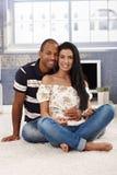 Houdend van paar dat thuis het glimlachen omhelst Stock Afbeeldingen