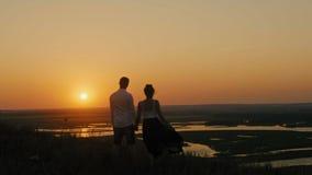 Houdend van paar - de moedige jonge mens en het mooie meisje bevinden zich op hoge heuvel en het kijken aan zonsondergangsilhouet stock videobeelden