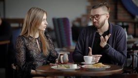 Houdend van paar die datum in cafetaria hebben Gelukkige man en vrouwenzitting bij de gediende lijst met voedsel en dranken het b stock footage