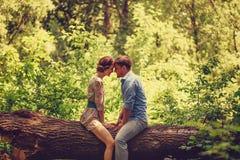 Houdend van paar die in de zomerpark rusten Stock Foto's