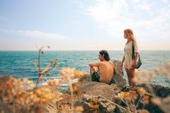 Houdend van paar die de zonsondergang op de overzeese kust bekijken De kust van de Zwarte Zee Stock Foto