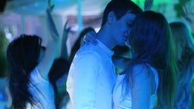 Houdend van paar die dicht bij elkaar bij disco op achtergrond van menigte in nachtclub dansen stock video